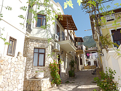 Thin alley in Kalkan Old Town with traditional townhouses on either side shaded from the sun